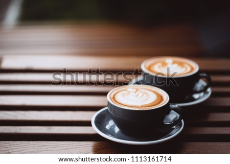 Two grey cups of cappuccino with latte art on wooden table. #1113161714
