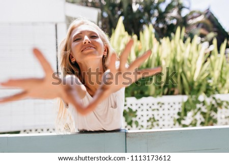 Emotional young woman fooling around in good warm day. Photo of carefree caucasian lady waving hands for photo and smiling. #1113173612