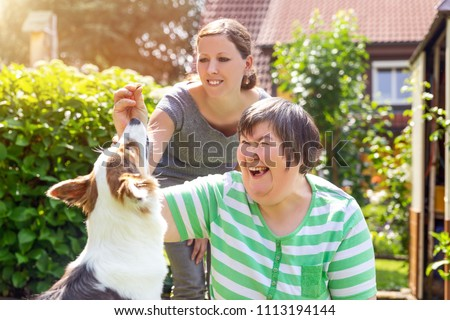 mentally disabled woman with a second woman and a companion dog, concept learning by animal assisted living Royalty-Free Stock Photo #1113194144