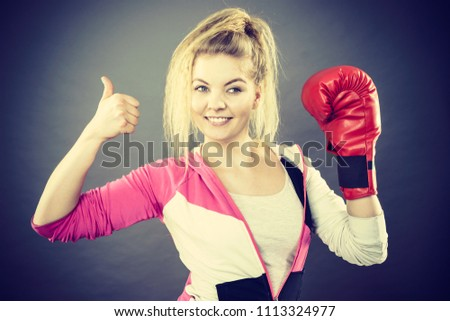 Sporty happy woman wearing red boxing gloves showing positive gesutre thumb up. Studio shot on dark background. #1113324977