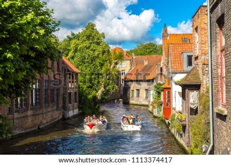 BRUGES, BELGIUM - JUNE 14, 2016: Tourist boat on canal in Bruges in a beautiful summer day, Belgium on June 14, 2016 #1113374417