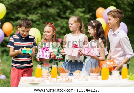 holidays, childhood and celebration concept - happy kids with gifts on birthday party at summer garden #1113441227