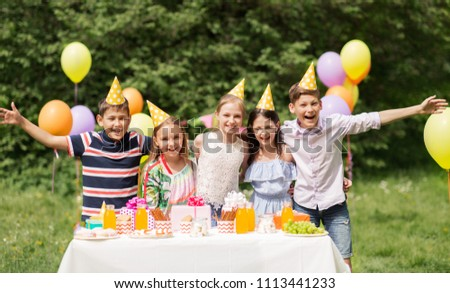 holidays, childhood and celebration concept - happy kids hugging on birthday party at summer garden #1113441233