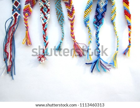 friendship bracelets made of thread with braids on white background #1113460313
