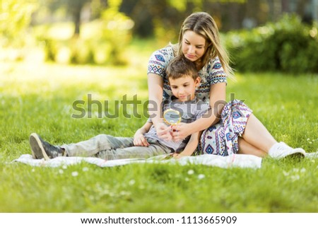 Young mother and son sitting on blanket in park  #1113665909