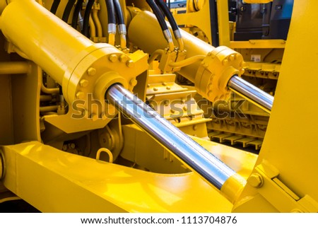 Hydraulic piston system for bulldozers, tractors, excavators, chrome plated cylinder shaft of yellow machine, construction heavy industry detail Royalty-Free Stock Photo #1113704876
