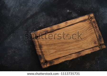 Rustic wooden serving tray on a dark scratched metal background, horizontal shot, top view, copyspace #1113735731