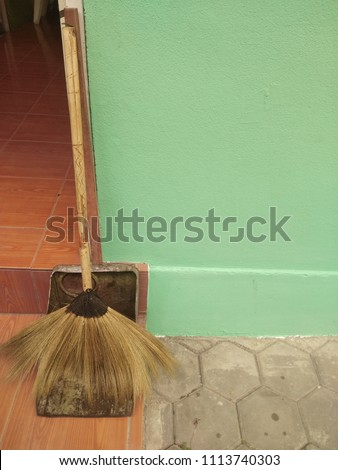 The broom and the dustpan are placed next to the door. #1113740303
