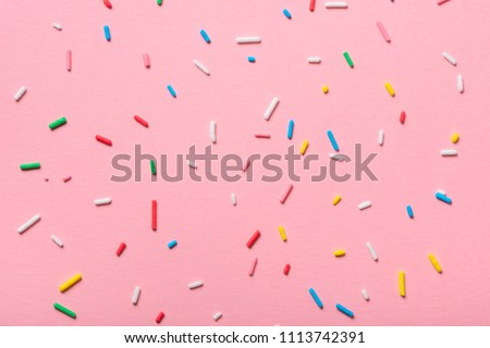 colorful sprinkles over pink background, decoration for cake and bakery  Royalty-Free Stock Photo #1113742391