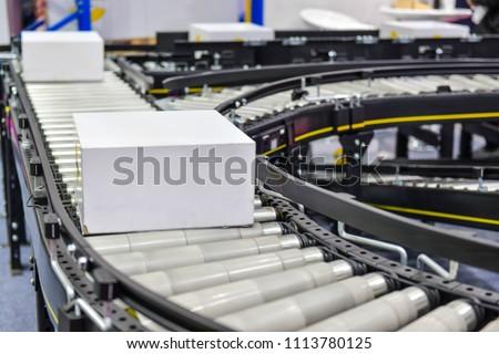 cardboard boxes on conveyor belt.parcels transportation system concept Royalty-Free Stock Photo #1113780125