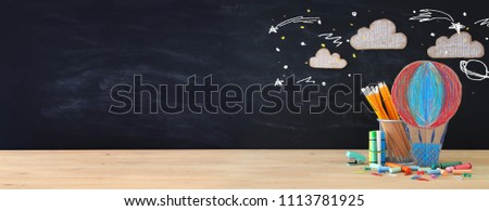 Back to school concept banner. hot air ballon and pencils in front of classroom blackboard