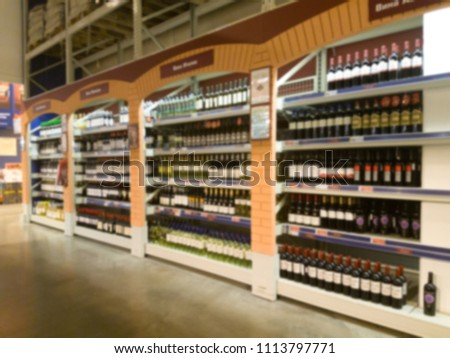 Blurred image of wine shelves display in supermarket. Defocused Rows of Wine Liquor bottles on the store shelf. Alcoholic beverage abstract background. Alcohol drink market concept. #1113797771