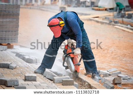 Construction worker cuts walkway curb with circular saw. Man Protect Hearing From Noise Hazards on the Job. Tiles piled in pallets on background. sawn paving slab next to the worker #1113832718