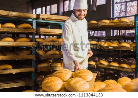 Baker. A young handsome bakery worker on the background of bread, takes bread from a stove with a wooden shovel. Industrial production of bakery products. a man in the baker's special clothing. Bakery #1113844133