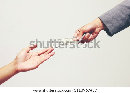 Businessman with smart suit holding money, american dollars, US dollar, USD. bills, offers dollar bank note in hand on gray background and giving money paid for Something by Cash in Business Concept.  #1113967439