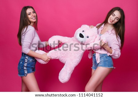Two beautiful girls on a pink background, in blue jeans #1114041152