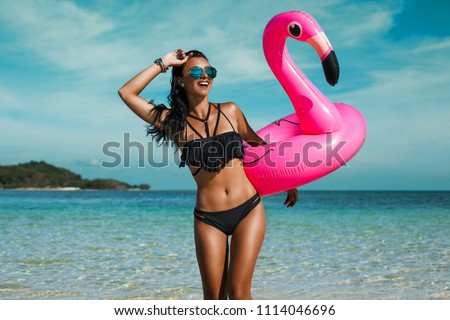 A beautiful sexy amazing young woman on the beach sits on an inflatable pink flamingo and laughs, has a great time, tanned perfect body, long hair, black bikini, fashion accessories, low key photo #1114046696