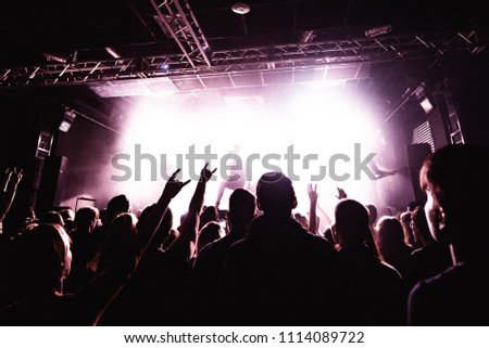 Silhouettes of people in a bright in the pop rock concert in front of the stage. Hands with gesture Horns. That rocks. Party in a club. Sold out. #1114089722