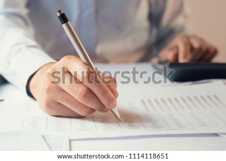 accountant working on desk to using calculator with penaccountant working on desk to using calculator with pen #1114118651