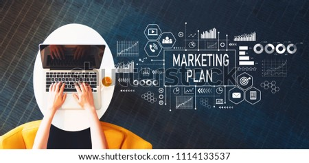 Marketing Plan with person using a laptop on a white table #1114133537