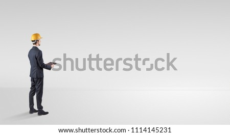 Young architect with construction helmet standing in an empty space and holding a plan #1114145231