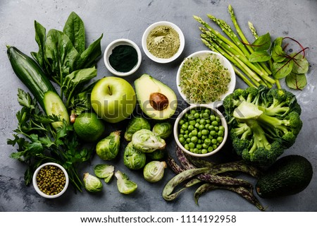 Healthy Green food Clean eating selection Protein source for vegetarians: avocado, asparagus, apple, broccoli, spinach, spirulina, green peas on gray concrete background #1114192958