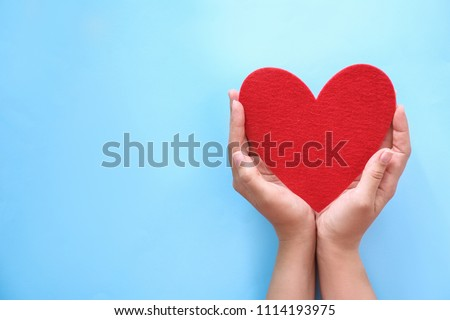 Young woman holding red heart on color background, top view #1114193975