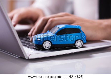 Close-up Of A Small Blue Car On Laptop Keypad #1114214825