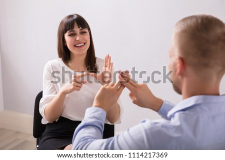 Smiling Young Woman And Man Talking With Sign Language On White Background