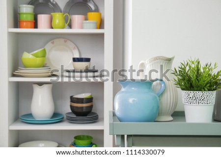White storage stand with colorful ceramic dishware indoors #1114330079