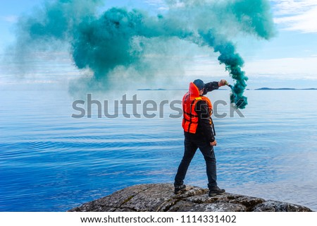 A man with a smoke torch. The rescue. Distress call. The man lights a smoke signal. A man in a life jacket. SOS. signal by smoke. Royalty-Free Stock Photo #1114331402