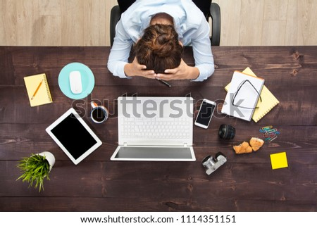 Stressed business woman sitting at office table and holding head in hands. Shot from above. #1114351151