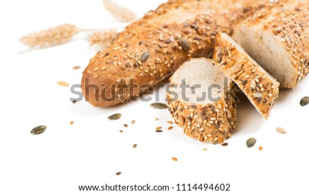 Baguettes bread whole and sliced with different seeds ( pumpkin, poppy, flax, sunflower, sesame, millet ) decorated with wheat ears isolated on white background.  Selective focus. #1114494602