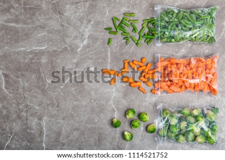 Plastic bags with different frozen vegetables on table, top view Royalty-Free Stock Photo #1114521752