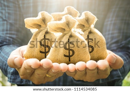 Money bags in man hand show savings money and savings to buy a home or buy real estate or car. Or show a home loan or divide the investment for retirement. Or for the future Concept of money. #1114534085