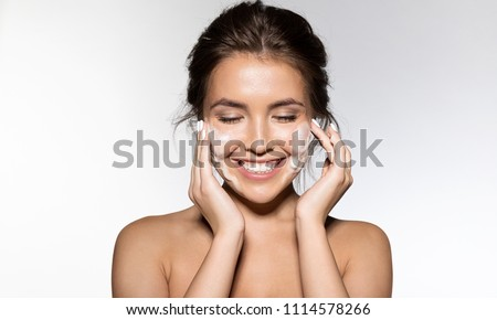 Portrait of cheerful laughing woman applying foam for washing on her face. Lovely brunette with attractive appearance. Skincare spa relax concept. Isolated on grey background #1114578266