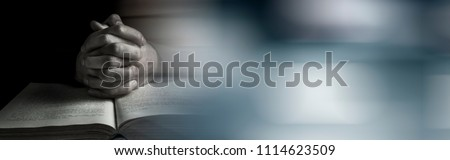 Hands of praying young man and Bible on a wooden desk background