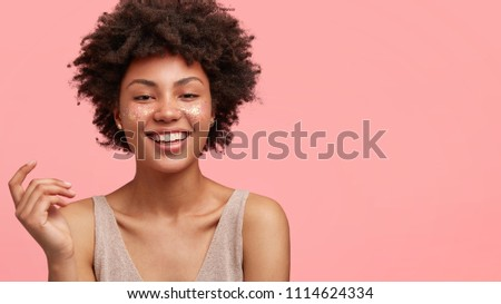 Adorable dark skinned female with glitter on face, smiles broadly at camera, expresses positive emotions, being satisfied with professional make up in beauty salon, isolated on pink background #1114624334