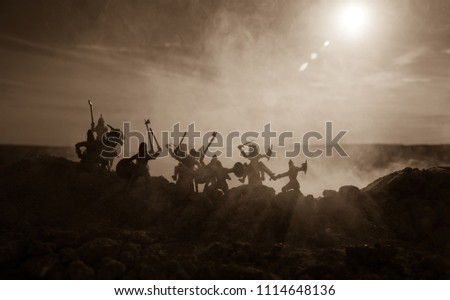 Medieval battle scene with cavalry and infantry. Silhouettes of figures as separate objects, fight between warriors on sunset foggy background. Selective focus #1114648136