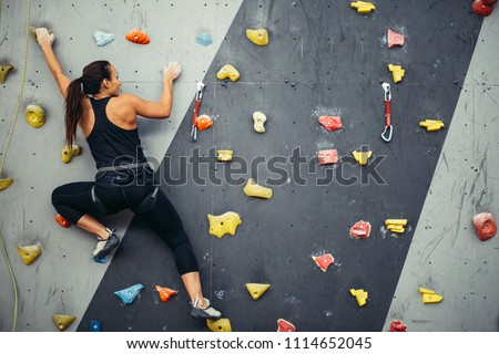 Active sporty woman practicing rock climbing on artificial rock in climbing s. Extreme sports and bouldering concept. #1114652045