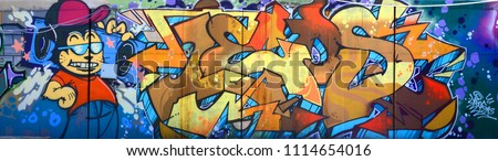 Street art. Abstract background image of a full completed graffiti painting in beige and orange tones with cartoon character #1114654016