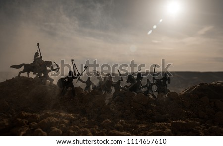 Medieval battle scene with cavalry and infantry. Silhouettes of figures as separate objects, fight between warriors on sunset foggy background. Selective focus #1114657610