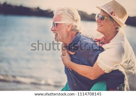 happy senior couple have fun and enjoy outdoor leisure activity at the beach. the man carry the woman on his back to enjoy together a retired lifestyle at the beach. smiling and laughing persons #1114708145