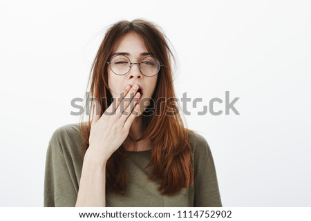 Mom woke up daughter very early. Shot of sleepy attractive caucasian woman with messy brown hair, wearing glasses, feeling tired after night without sleep, yawning, covering opened mouth with palm #1114752902