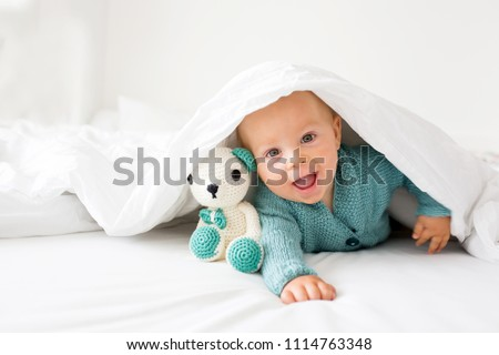 Little cute baby boy, child in knitted sweater, holding knitted toy, smiling happily at camera in white sunny, bright bedroom #1114763348