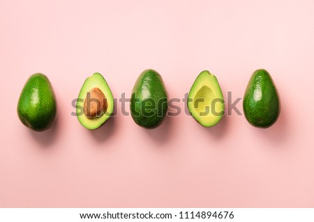 Organic avocado with seed, avocado halves and whole fruits on pink background. Top view. Pop art design, creative summer food concept. Green avocadoes pattern in minimal flat lay style #1114894676