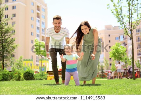 Parents supporting their baby daughter while she learning to walk outdoors #1114915583