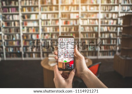 Close up female hands holding mobile. She taking photo of table with books in library