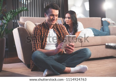 Modern family. Full length portrait of happy young man is touching screen of tablet with joy. He is sitting on floor and smiling. Woman is lying on sofa with smartphone  #1114924763