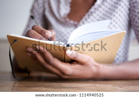 Close up partial portrait of black female author at home writing in journal Royalty-Free Stock Photo #1114940525